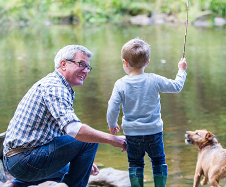little boy fishing with his grandpa and dog