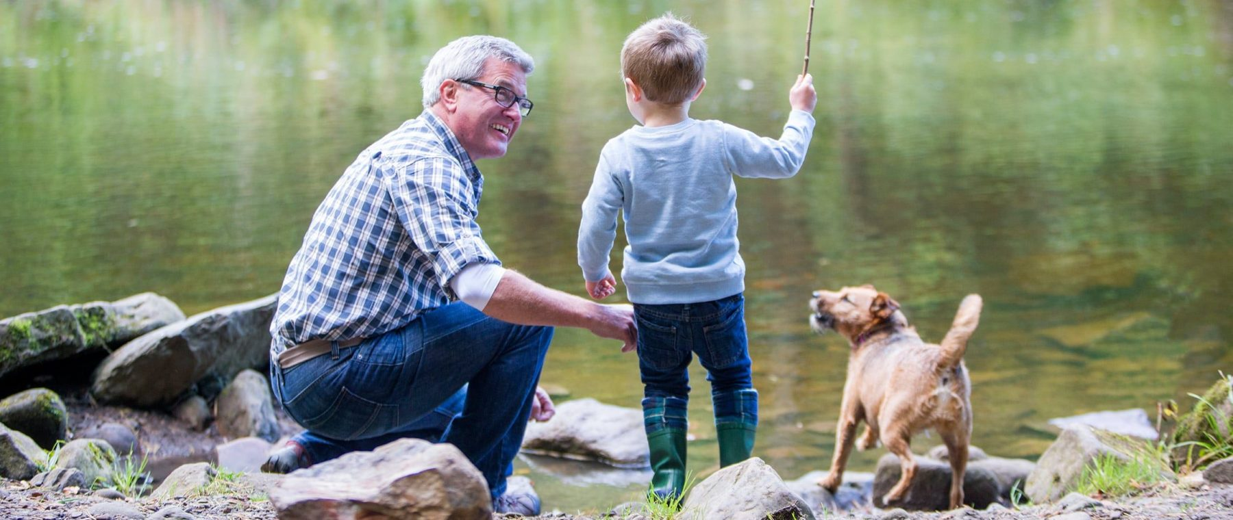 little boy fishing with grandpa and dog